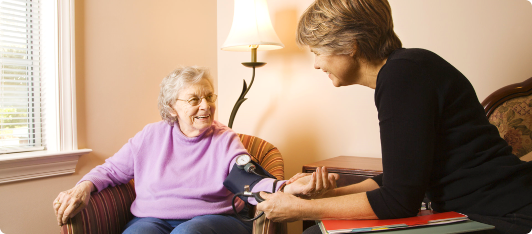 caregiver measuring blood pressure of an elder